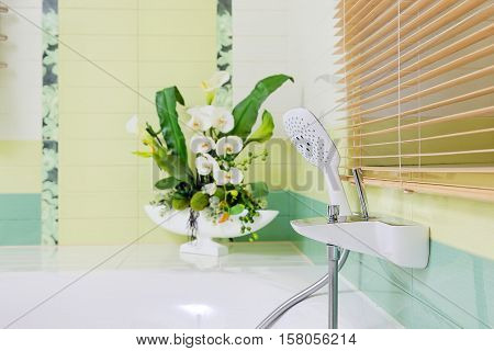 Beautiful white faucet on bathtub with flowers decor