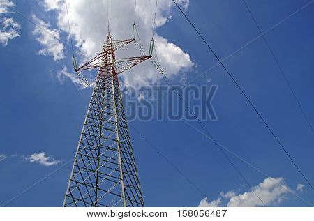 High Voltage Power Lines intersect at a large metal Utility pole in Maine against a blue sky