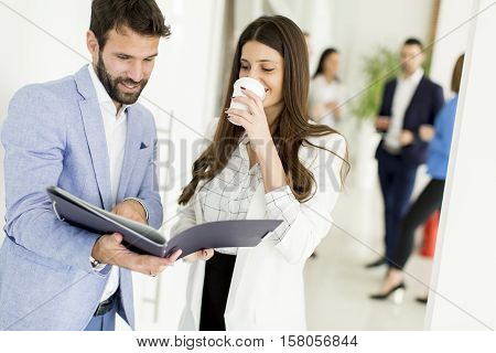 Young business partners analyze the business results while business woman drinking coffee and young business people talking in the background