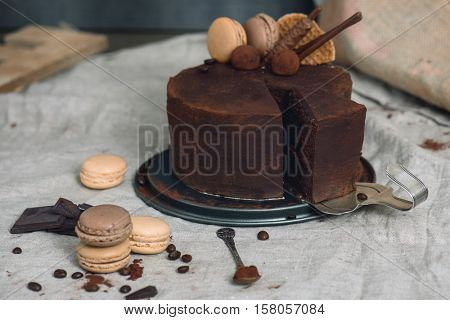 Chocolate cake covered with cocoa powder, one slice on a vintage silver cake server. French macarons and chocolate around
