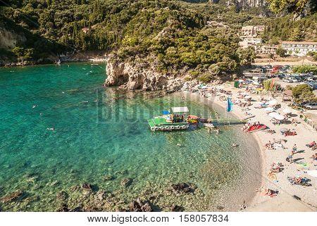 CORFU ISLAND, GREECE - August 10, 2014: Beautiful beach of Paleokastritsa. Tourists enjoying a nice summer day at the beach. Kerkyra island