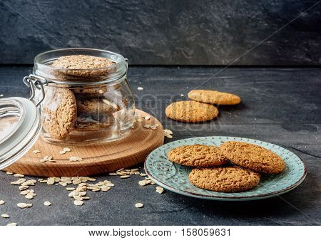 Oat cookies lay on a plate and bank with oatmeal cookies standing on a wooden board.