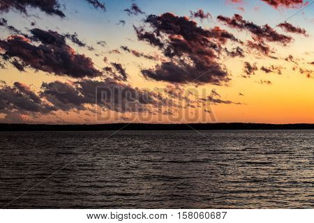 Clouds drifting along over a lake at sunset.
