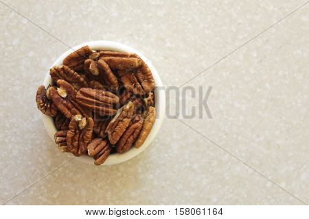 Pecans in a container on a kitchen countertop. Photographed from above with container positioned left.