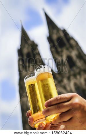 Two glasses of beer named Koelsch with cathedral of Cologne in background Germany