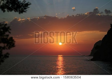 Beautiful gold and orange sunset with a sailboat sailing through the beam of sunlight.