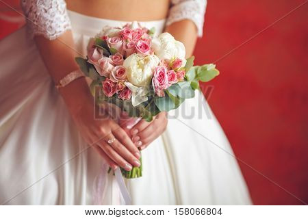 Young bride in wedding dress with bouquet of peony and roses, closeup, vintage toned