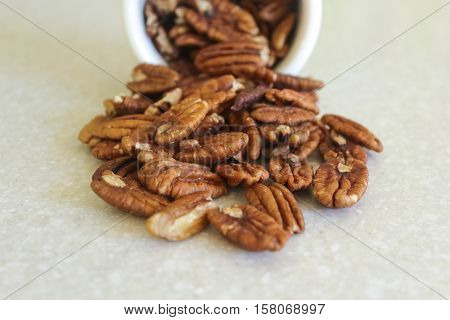 Pecans spilling out of a container on a kitchen countertop. Focus on pecans in center of image.