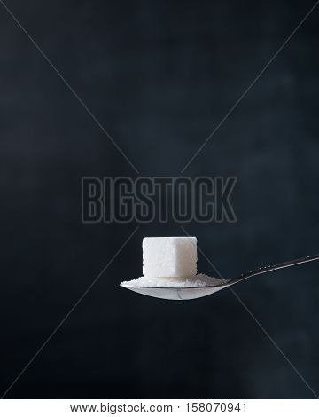 Sugar cube and crystals in a silver teaspoon on the dark background