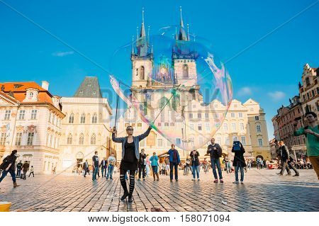 Prague, Czech Republic - October 15, 2014: Unidentified Young Woman Makes Soap Bubbles In Old Town Square - Staromestske Namesti. Church Of Our Lady Before Tyn On Background.