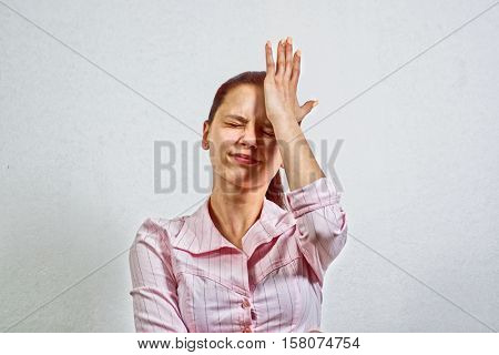Unhappy Young Adult Female Wearing Blouse, Hitting Her Head, Eyes Closed, Gesturing She Has Made a Big Mistake