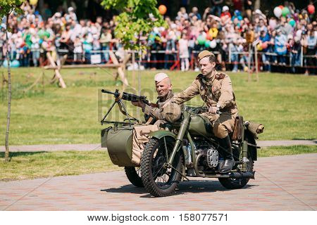 Gomel, Belarus - May 9, 2016: Two Men In Soldiers Soviet Uniform With Machine Gun On Tricycle Sidecar. Scene Of Historical Reenactment Of WW2 Time On Victory Day 9 May.