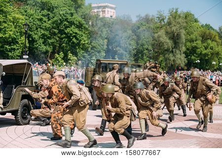Gomel, Belarus - May 9, 2016: The Group Of Reenactors In Russian Soviet Soldiers Uniform Running With Guns. Scene Of Reenactment Battle Of WW2 Time, Celebration Victory Day 9 May.