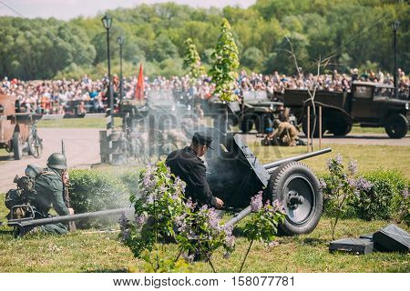 Gomel, Belarus - May 9, 2016: Back View Of Two Wehrmacht Soldiers Reenactors Recreate The Battle Of WW2 With Guns. Scene Of Historical Reenactment  On Celebrating Victory Day 9 May.
