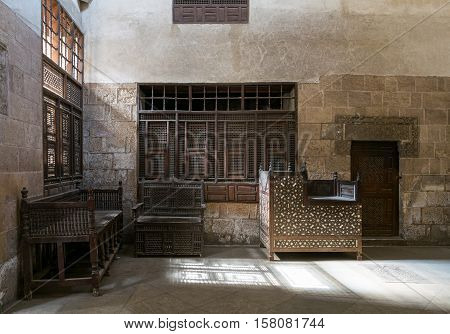 Cairo, Egypt - November 19, 2016: One of the rooms of El Sehemy house an old Ottoman era house in Cairo originally built in 1648 with interleaved wooden windows (Mashrabiya) and arabisk wooden couches