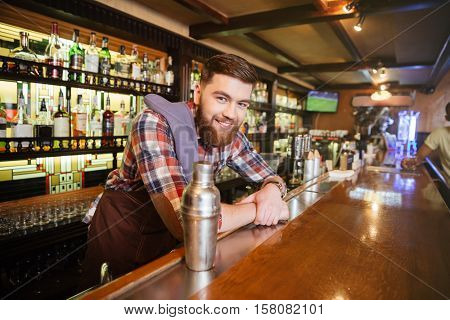 Portrait of cheerful young bartender standing and smiling in bar