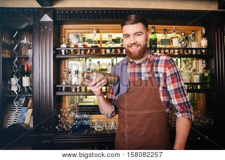 Happy handsome bartender in brown apron standing and holding shaker in bar
