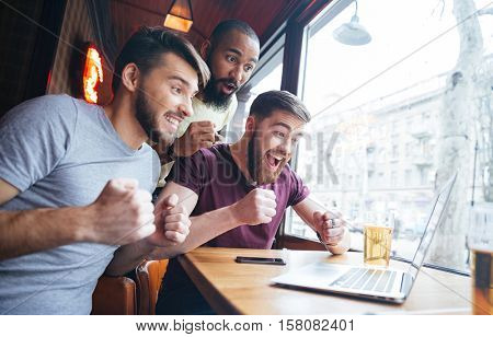 Three cheerful excited young men watching match on laptop and supporting their team sitting in bar