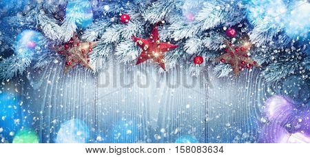 Christmas decoration with stars on wooden background with color bokeh effect. Holiday background