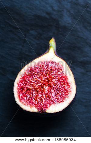 Whole figs and one fig sliced in half on black background macro.