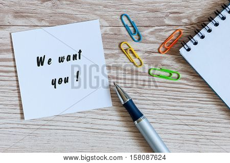 We Want You - card or notice on white workplace background with offise suplies. poster