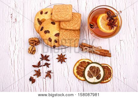 Cup Of Tea With Cinnamon, Lemon And Other Seasonings Stands On White Table Between Christmas Cookies