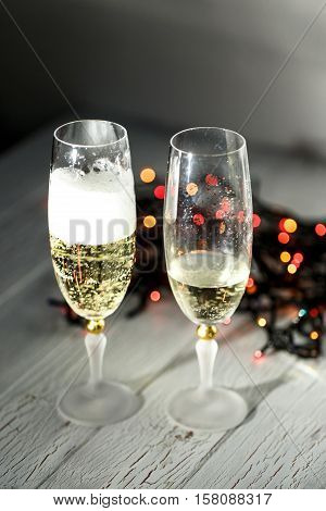 Champagne With Foam In A Glass Standing Behind Christmas Garland