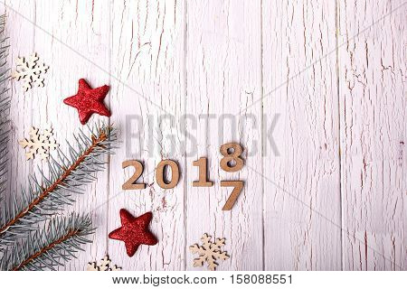 Red Christmas Stars And Fir Branches Surround Wooden Numbers 2016 And 2017 On White Table