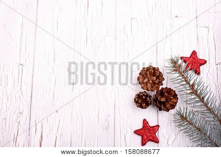 Conifer Cones, Fir Branches And Red Stars Lie On White Wooden Table