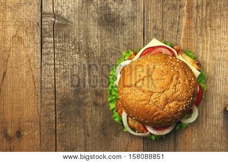 Top view gourmet  hamburger on wooden background. Fastfood meal. Vintage toned