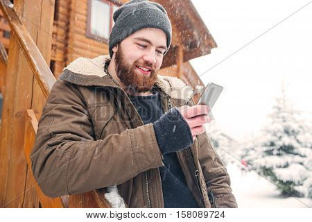 Smiling bearded young man standing and using smartphone outdoors in snowy weather in winter