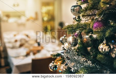 Closeup of tinsel and decorations hanging from the branches of a Christmas tree in a home during the festive season
