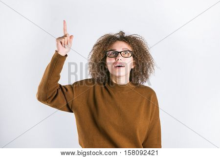 Funny girl in glasses with a raised finger.