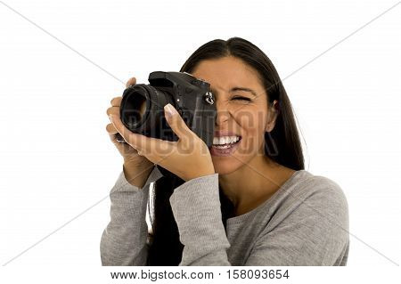 portrait of young beautiful and exotic hispanic photographer woman smiling happy and relaxed isolated on white background taking photos with photographic reflex camera excited and cheerful