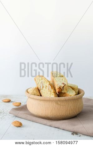 Italian cantuccini cookies in a bowl with almonds. Traditional italian almond cookies biscotti on white background. Homemade cookies with space for text on wooden table. Selective focus. Copy space.