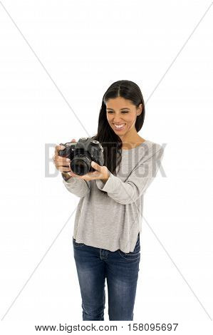 portrait of young beautiful and exotic hispanic photographer woman smiling happy and relaxed isolated on white background looking photographic reflex camera excited and cheerful