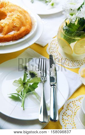 Yellow summer table setting with lemon bundt cake white plates teapot and chrysanthemum flowers in a glass vase