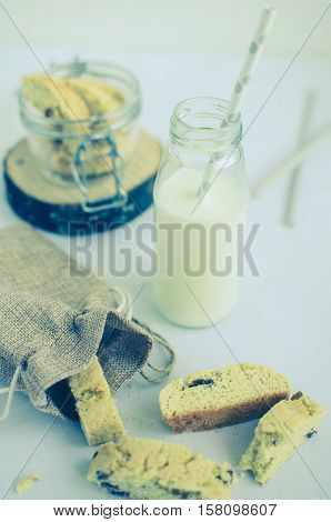 Homemade raisins cookies with bottle of milk on white background. Freshly baked raisin cookie. Healthy breakfast raisins cookies and milk. Tasty cookies for an afternoon snack. Selective Focus.