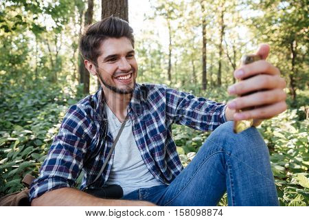 Guy sitting and makes selfie in forest. near the tree. smiling man
