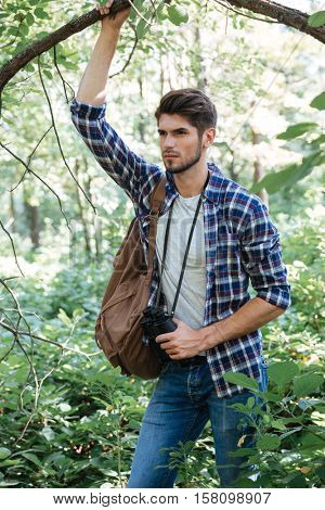 Man with backpack near the tree. clinging to a tree. mand in shirt with binoculars