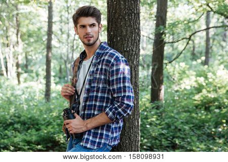 Man in shirt with binoculars and backpack near the tree. stands sideways. looking away