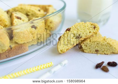 Homemade raisins cookies with glass of milk on white background. Freshly baked raisin cookie. Healthy breakfast raisins cookies and milk. Tasty cookies for an afternoon snack. Selective Focus.