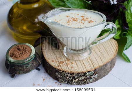 Classic European white sauce Bechamel in saucer with nutmeg basil and olive oil on white background. Bechamel sauce for traditional European dishes. Italian food concept. Selective focus.