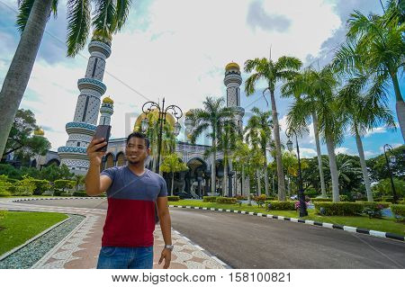 Bandar Seri Begawan,Brunei-Nov 11,2016:Tourist taking pictures with handphone of the Jame'asr Hassanil Bolkiah Mosque,Bandar Seri Begawan Brunei,it is the largest mosque in Brunei Darussalam.