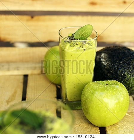 Organic vegan green detox shake or smoothie made of apple avocado and banana with chia and leaf of mint. With fresh fruits on the wooden background. Selective focus.