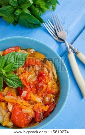 Italian peperonata: roasted bell pepper with basil in a bowl on blue wooden background. Pepper lecho stew ragout. Peperonata - traditional dish of italian cuisine. Italian cuisine concept.