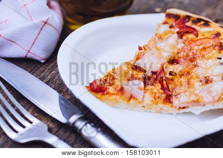 Slice of delicious fresh pizza with ham mushrooms tomatoes pepper and melting cheese on a white plate on old wooden table. Rustic style. Homemade pizza ready to eat. Italian food concept. Top view.