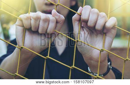 Asia girl hands steel net behind cage.