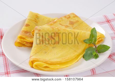 plate of empty folded pancakes on checkered dishtowel - close up
