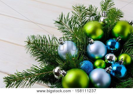Christmas background with blue green and pale blue ornaments. Christmas decoration with shiny bauble hanging. Copy space.